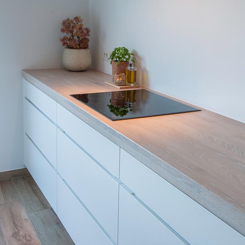 Strak keuken ontwerp witte keuken met eiken whitewash werkblad met zwart inductievuur