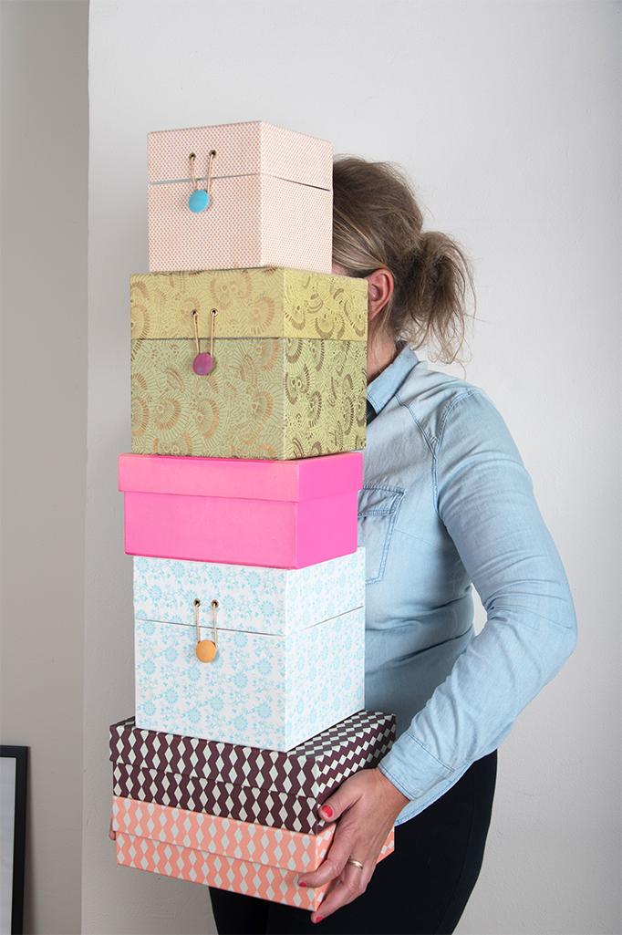 Zaakvoerder Sofie Wolf staat met een stapel gekleurde dozen