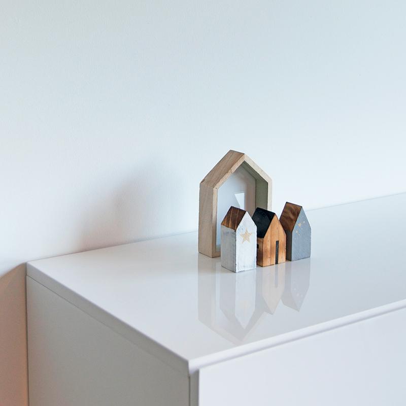 Decoratieve huisjes op witte kast in leefruimte